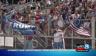 "Several high school students who waved a Donald Trump flag and a ""Betsy Ross"" 13-star flag at an inner city Grand Rapids football game Friday night are being criticized as racist. (WOOD-TV)"