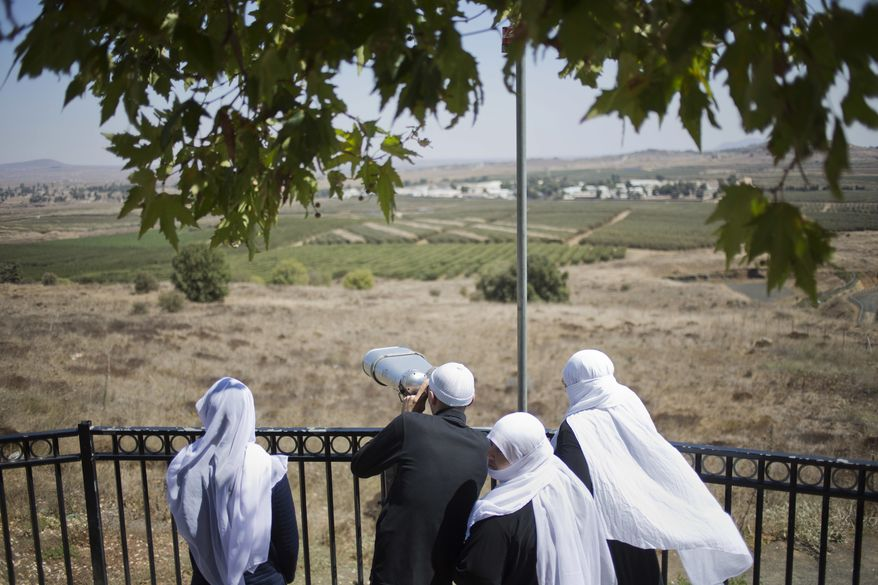 A Druze family, celebrating the Eid al-Adha holiday, look towards Syria's Quneitra province as they visit an observation point in the Israeli-controlled Golan Heights, Tuesday, Sept. 13, 2016. Israel is denying Syrian government claims that its forces shot down a warplane and a drone near the Israeli-controlled part of the Golan Heights. Israeli warplanes have conducted several air raids on Syrian army positions over the past weeks after stray shells hit the Israeli-occupied area. (AP Photo/Ariel Schalit)
