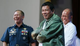 """Philippine President Rodrigo Duterte wears a pilot's jacket which was presented to him during his """"Talk with the Airmen"""" on the anniversary of the 250th Presidential Airlift Wing Tuesday, Sept. 13, 2016 at the Philippine Air Force headquarters in suburban Pasay city, southeast of Manila, Philippines. On Monday, President Duterte, in his first public statement opposing the presence of American troops, said he wants U.S. forces out of his country's south and blamed America for inflaming Muslim insurgencies in the region.(AP Photo/Bullit Marquez)"""