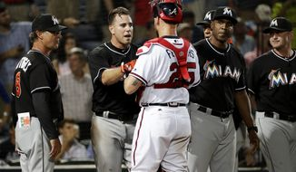 Miami Marlins' Jose Fernandez, second from left, talks with Atlanta Braves catcher Tyler Flowers after Atlanta reliever Jose Ramirez threw inside to Fernandez in the seventh inning of a baseball game in Atlanta, Wednesday, Sept. 14, 2016. The benches for both teams emptied in the seventh inning after the pitch to Fernandez, who had been knocked to the ground by a pitch from Teheran in the fifth. No punches were thrown and Ramirez was ejected. (AP Photo/David Goldman)