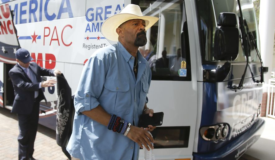 In this Monday, Sept. 12, 2016, photo, David A. Clarke Jr., Sheriff of Milwaukee County, Wis., and Donald Trump supporter, arrives on the Great America PAC bus for a town hall meeting in Lake Mary, Fla. The Great America PAC is rolling through battleground states, opening offices and registering voters. Presidential hopefuls often embark on bus tours to meet voters across the country. This time, a super PAC is standing in for Republican nominee Donald Trump. (AP Photo/John Raoux)