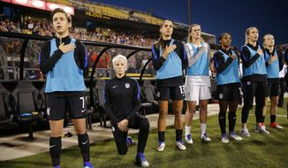 United States' Megan Rapinoe, second from left, kneels during the playing of the national anthem before the soccer match against Thailand, Thursday, Sept. 15, 2016 in Columbus, Ohio.  Rapinoe did not start the game against Thailand at Mapfre stadium. She knelt from a spot near the bench while the fellow reserves around her stood. (Kyle Robertson/The Columbus Dispatch via AP)