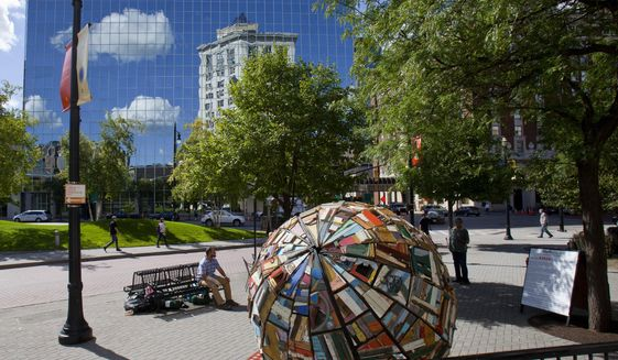 "Loren Naji's ArtPrize entry ""Emoh: sculpture/time capsule & temporary home"" outside Kilwin's Chocolates & Ice Cream at the McKay Tower, in Grand Rapids, Mich., on Wednesday, Sept. 14, 2016. Naji, who is from Cleveland, Ohio, plans to live inside his entry for the duration of ArtPrize. The word Emoh is home spelled backwards. He built Emoh using debris from abandoned homes and looks to raise awareness for homelessness. (Cory Morse/The Grand Rapids Press-MLive.com via AP)"