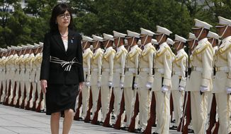 FILE - In this Aug. 4, 2016 file photo, Japan's new Defense Minister Tomomi Inada inspects a honor guard on her first day at the Defense Ministry in Tokyo. Inada, who holds her first meeting with U.S. counterpart Ash Carter on Thursday, Sept. 15, in Washington, D.C., leapfrogged over more senior lawmakers to the defense post in a Cabinet reshuffle on Aug. 3. The 57-year-old lawyer has attracted attention for questioning mainstream accounts of Japanese atrocities during World War II and the fairness of the postwar Tokyo war crimes trials. (AP Photo/Shuji Kajiyama, File) **FILE**