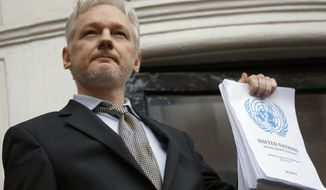 Julian Assange holds a U.N. report as he speaks on the balcony of the Ecuadorian Embassy in London in this Feb. 5, 2016  file photo. (AP Photo/Frank Augstein, File)