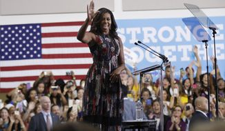 First lady Michelle Obama waves during a campaign rally in support of Democratic presidential candidate Hillary Clinton and vice presidential candidate, Sen. Tim Kaine, D-Va., Friday, Sept. 16, 2016, at George Mason University in Fairfax, Va. (AP Photo/Manuel Balce Ceneta)
