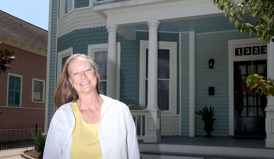 In this Sept. 1, 2016 photo, Julie Baker poses outside her renovated Victorian home in Galveston, Texas. Baker and her husband, Franklin, took advantaged of Galveston's tax exemption program when they decided to buy and renovate the home. (Jennifer Reynolds/The Galveston County Daily News via AP)