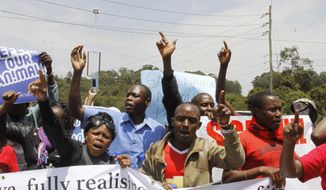 """Kenyans hold up signs as they attend a protest to protect the Nairobi National Park in Nairobi, Friday, Sept. 16, 2016. Dozens of angry people have marched in the Kenyan capital Nairobi to protest plans to build a railway line over a national park. The protesters included conservationists and others who wore T-shirts and carried banners saying """"don't rape our park."""" (AP Photo/Khalil Senosi)"""