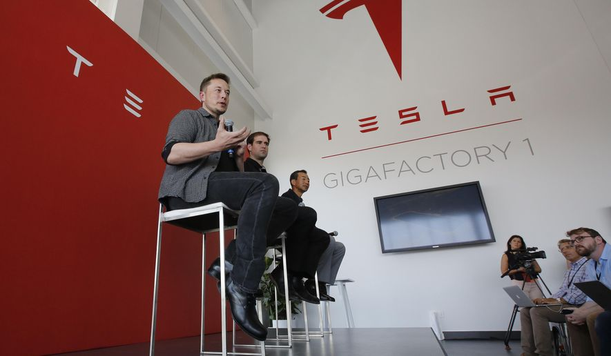 Elon Musk, CEO of Tesla Motors Inc., left, discusses the company's new Gigafactory in Sparks, Nevada, in this July 26, 2016, file photo. (AP Photo/Rich Pedroncelli, file) **FILE**
