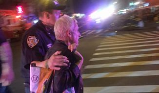 A police officer escorts an injured man away from the scene of a possible explosion on West 23rd Street in New York. Authorities said dozens suffered minor injuries. (AP Photo/Nico Maounis)