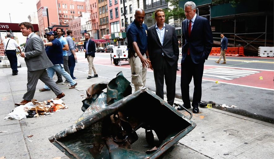 New York Mayor Bill de Blasio (right) and New York Gov. Andrew Cuomo (center) looked over a mangled construction toolbox on Sunday while touring the site of an explosion on Saturday night that injured 29 people. (Associated Press)