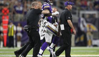 Minnesota Vikings running back Adrian Peterson (28) is helped off the field after getting injured during the second half of an NFL football game against the Green Bay Packers Sunday, Sept. 18, 2016, in Minneapolis. (AP Photo/Andy Clayton-King)
