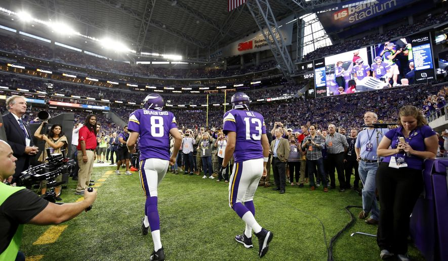 Minnesota Vikings quarterbacks Sam Bradford (8) and Shaun Hill (13) walk to the field before an NFL football game against the Green Bay Packers Sunday, Sept. 18, 2016, in Minneapolis. (AP Photo/Andy Clayton-King)
