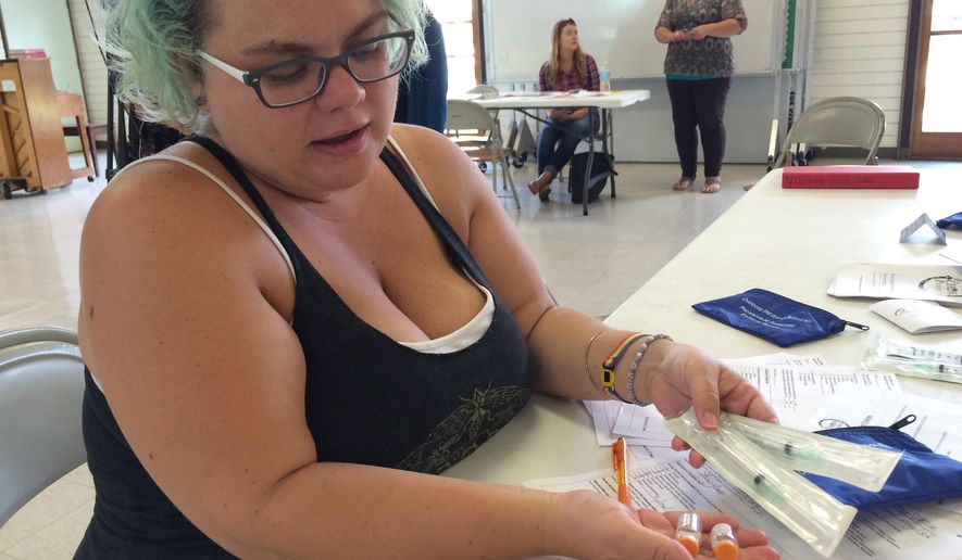 In this Sept. 12, 2016 photo, Stacy Lenze, a community health outreach worker, holds a vial of naloxone and syringes in Honolulu, Hawaii, that is being distributed in Hawaii to combat drug overdoses. A new Hawaii law allows groups to distribute the life-saving medication. Overdose deaths from prescription painkillers have soared, claiming 165,000 lives in the U.S. since 2000. (AP Photo/Cathy Bussewitz)
