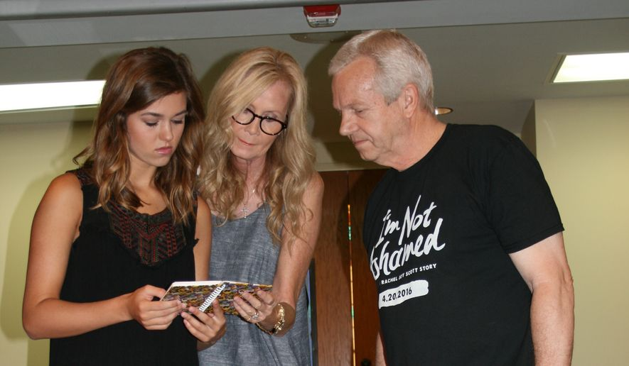 """Sadie Robertson (left), her grandmother Chrys Howard and """"I'm Not Ashamed"""" co-producer Benny Proffitt examine the journal that belonged to Rachel Joy Scott, the first victim shot to death at Columbine, and whose Christian faith inspired the making of the film scheduled for release Oct. 21.  (Tom Quimby)"""