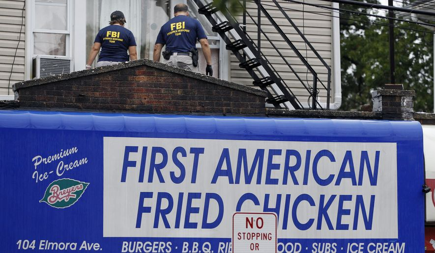 FBI agents walk around the roof outside an apartment during an investigation at a building Monday, Sept. 19, 2016, in Elizabeth, N.J. FBI agents are searching the apartment that is tied to Ahmad Khan Rahami wanted for questioning in the New York City bombing. (AP Photo/Mel Evans)