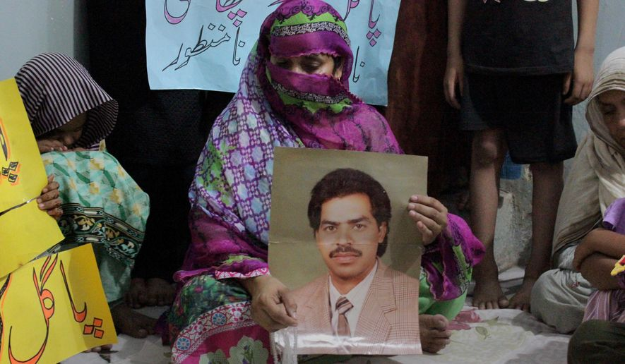 Safia Bano displays the picture of her husband Imdad Ali, a death row prisoner, while she sits with other family members in Burewala, in central Pakistan, Sunday, Sept. 18, 2016. A rights group and the family of Ali, a mentally ill man on death row in Pakistan have pleaded with the government to halt his execution. Imdad Ali was convicted in a 2001 murder case and has exhausted all appeals. (AP Photo/Asghar Ali)