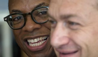 Clay Hamilton, left, and Adrian Coman, a US-Romanian gay couple who got married in Belgium and seek legal recognition of their status in Romania smile during an interview with the Associated Press in Bucharest, Romania, Friday, July 22, 2016. Commentators predict the court, scheduled to rule Tuesday on the marriage of U.S. graphic designer Claibourn Robert Hamilton and Romanian human rights activist Adrian Coman, will vote against the motion, amid opposition from the influential Romanian Orthodox Church and public disapproval of same-sex relationships.(AP Photo/Vadim Ghirda)