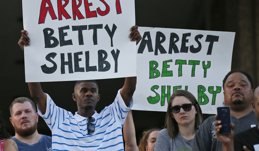 "People hold signs at a ""protest for justice"" over Friday's shooting death of Terence Crutcher, sponsored by We the People Oklahoma, in Tulsa, Okla., Tuesday, Sept. 20, 2016. (AP Photo/Sue Ogrocki)"