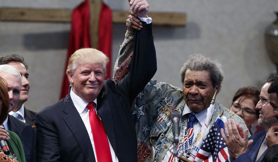 Boxing promoter Don King holds up the hand of Republican presidential candidate Donald Trump during a visit to the Pastors Leadership Conference at New Spirit Revival Center, Wednesday, Sept. 21, 2016, in Cleveland, Ohio. (AP Photo/ Evan Vucci)