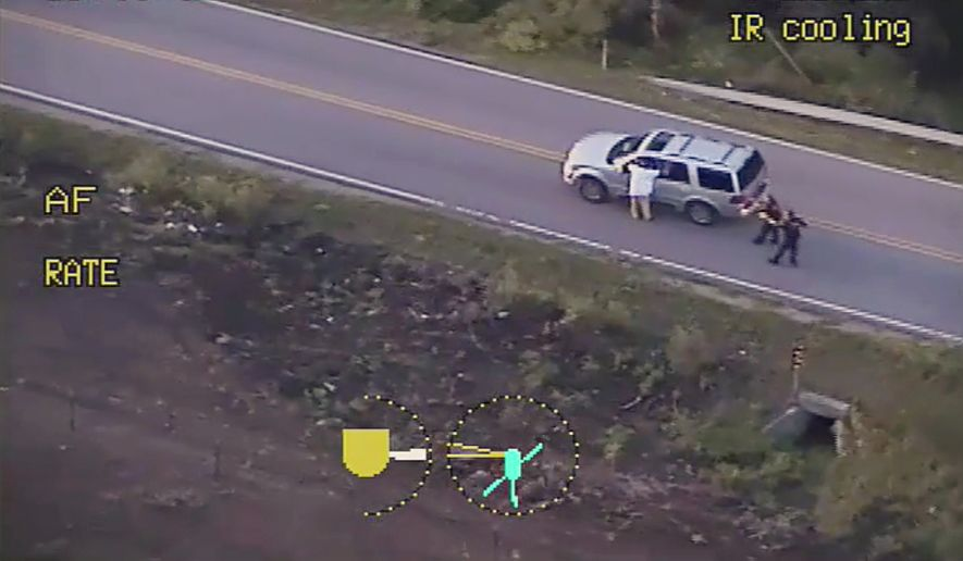 In this photo made from a Sept. 16, 2016, police video, Terence Crutcher, left, with his arms up is pursued by police officers as he walks next to his stalled SUV moments before he was shot and killed by one of the officers in Tulsa, Okla. Recent shootings by police raise a fundamental question: In the moments after officers shoot someone, how soon can medical aid be given? (Tulsa Police Department via AP, File)