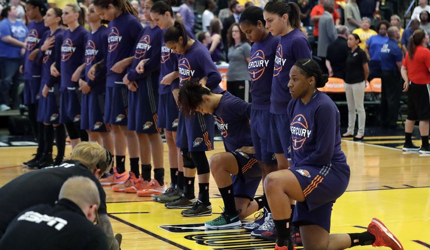 Phoenix Mercury's Kelsey Bone, right, and Mistie Bass, second from right, kneel during the playing of the national anthem before the start of a first round WNBA playoff basketball game against the Indiana Fever, Wednesday, Sept. 21, 2016, in Indianapolis. (AP Photo/Darron Cummings)