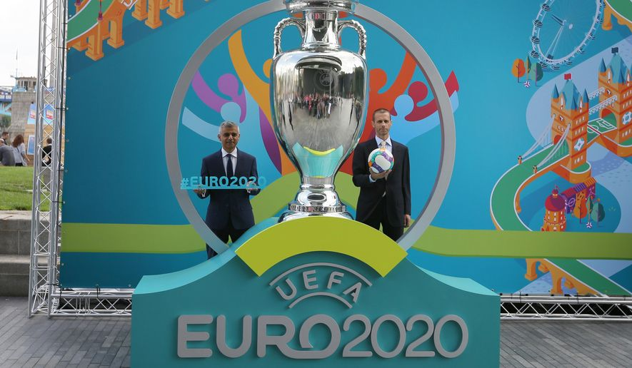 Mayor of London Sadiq Khan, left, and UEFA president. Aleksander Ceferin pose with a version of the logo on display during the launch event of UEFA Euro 2020 and the unveiling of the tournament brand and the London host city logo at City Hall, in London, Wednesday Sept. 21, 2016. (AP Photo/Tim Ireland)