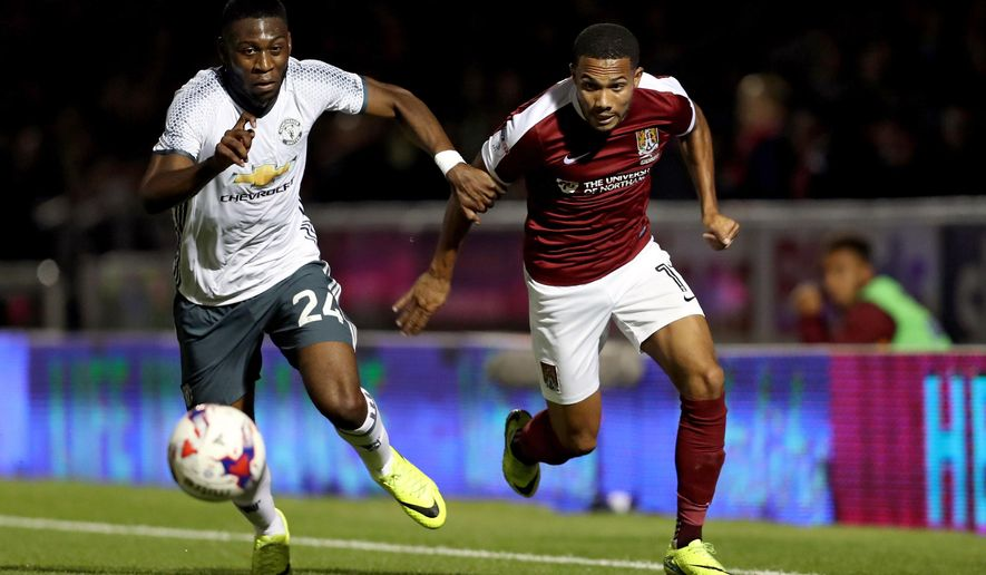 Northampton Town's Kenji Gorre, right, and Manchester United's Timothy Fosu-Mensah run towards the ball during the English League Cup third round soccer match at Sixfields Stadium, Northampton, England, Wednesday Sept. 21, 2016. (David Davies/PA via AP)