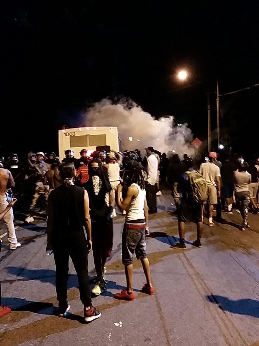 Police fire tear gas into the crowd of protesters on Old Concord Road late Tuesday night, Sept. 20, 2016, in Charlotte, N.C. A black police officer shot an armed black man at an apartment complex Tuesday, authorities said, prompting angry street protests late into the night. The Charlotte-Mecklenburg Police Department tweeted that demonstrators were destroying marked police vehicles and that approximately 12 officers had been injured, including one who was hit in the face with a rock.  (Ely Portillo/The Charlotte Observer via AP)