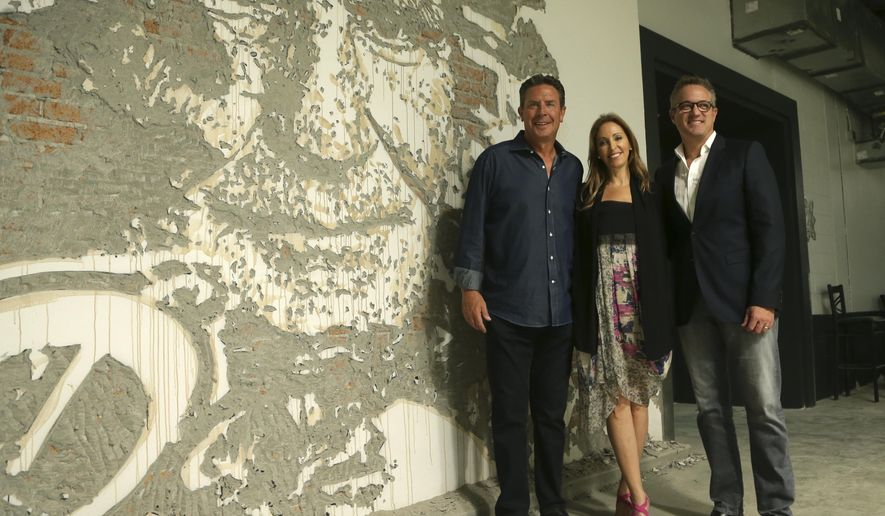 In this Tuesday, Sept. 20, 2016 photo, former Miami Dolphins quarterback Dan Marino, left, Jessica Goldman Srebnick, CEO of Goldman Global Arts, center, and Tom Garfinkel, Miami Dolphins president and CEO, right, pose for a photo next to artwork by the Portuguese artist Alexandre Farto, known as Vhiles, of former Dolphins head coach Don Shula, at Hard Rock Stadium in Miami Gardens, Fla. When the Miami Dolphins play their home opener against the Cleveland Browns, it will be in a refurbished stadium that features 29,000 square feet of new, original wall art from artists from all over the world. (AP Photo/Lynne Sladky)