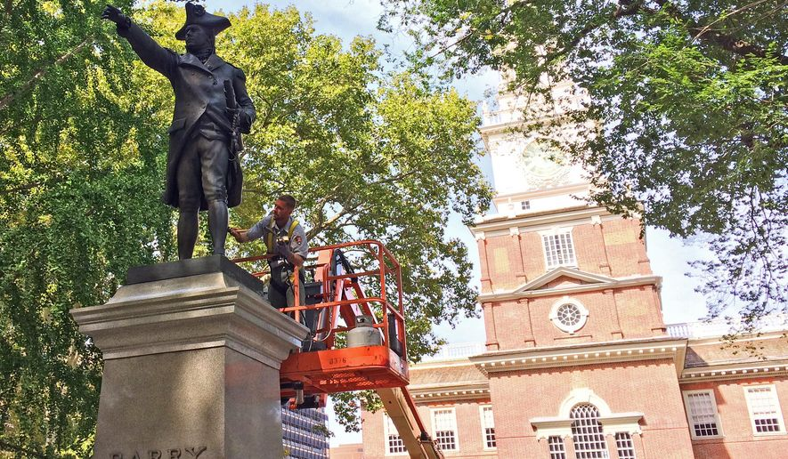 Ryan Neill, a National Park Service employee from Gettysburg National Military Park, brushes wax onto a statue of U.S. Navy Commodore John Barry on Wednesday, Sept. 21, 2016, outside Independence Hall in Philadelphia. Sculptor Samuel Murray's much-photographed bronze statues of George Washington and Commodore John Barry outside Philadelphia's Independence Hall will shine brighter after their September 2016 cleaning, which the National Park Service says is required about every five years. (AP Photo/Kristen De Groot)