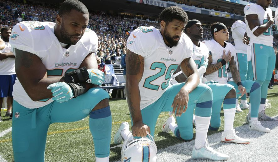 FILE - In this Sept. 11, 2016, file photo, from left, Miami Dolphins' Jelani Jenkins, Arian Foster, Michael Thomas, and Kenny Stills kneel during the singing of the national anthem before an NFL football game against the Seattle Seahawks in Seattle. Miami Dolphins safety Michael Thomas and linebacker Jelani Jenkins say they received death threats through social media following their national anthem protest, but remain committed to push for better race relations, which is why they helped organize a town hall with police and youth leaders. (AP Photo/Stephen Brashear, File)