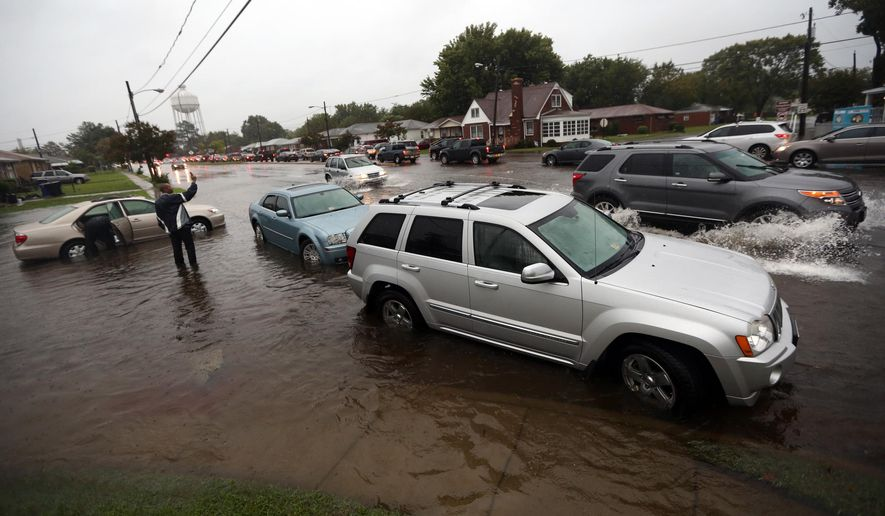 Cars stall out in floodwater on Effinghman Street in Portsmouth, Va.,, as others drive by in a steady rain, Wednesday, Sept. 21, 2016. A stalled weather system and the remnants of Tropical Storm Julia have brought days of rain and localized flooding to the region through Wednesday. (Steve Earley/The Virginian-Pilot via AP)
