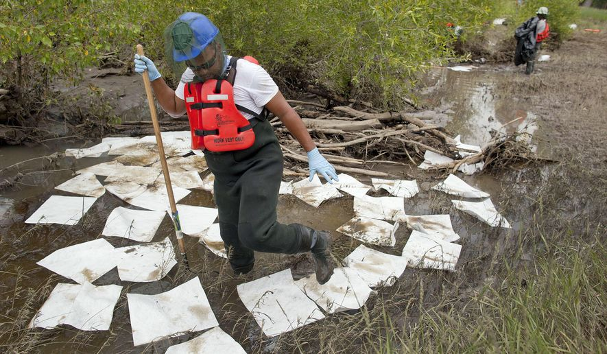 FILE - In this July 11, 2011, file photo, an oil spill crew worker for Oil Mop Emergency Response steps out of a ring of absorbent pads along a flood plain of the Yellowstone River where oil was found collected, near Laurel, Mont. Exxon Mobil Corporation has agreed to pay about $12 million for damages caused by the 2011 pipeline break that spilled gallons of crude into Montana's Yellowstone River, officials said Wednesday, Sept. 21, 2016. (AP Photo/Julie Jacobson, File)