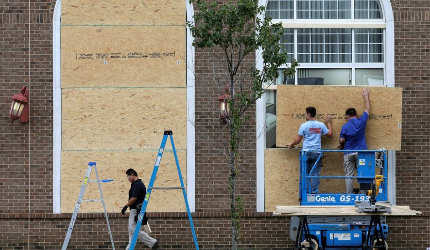 Workers cover windows with plywood at a downtown hotel after a second night of violence in the wake of Tuesday's fatal police shooting of Keith Lamont Scott in Charlotte, North Carolina. (Associated Press)