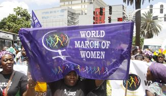 Women from Kenya, Uganda, Tanzania, Rwanda and Burundi participate in the world march of woman in Nairobi, Kenya Tuesday, Oct. 13, 2015. The women marched to protest against early marriage, sexual harassment, Female Genital Mutilation and all forms of violence and inequality against women. (AP Photo/Khalil Senosi)