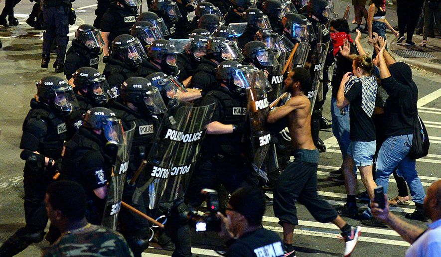 Charlotte-Mecklenburg police officers begin to move protesters down a street in Charlotte, N.C., Wednesday, Sept. 21, 2016. (Jeff Siner/The Charlotte Observer via AP)