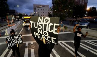 Protesters block an intersection near the Transit Center as they march uptown in Charlotte, N.C., Wednesday, Sept. 21, 2016. With officials refusing to release any video of the Tuesday shooting of 43-year-old Keith Lamont Scott, anger built as two starkly different versions emerged: Police say Scott disregarded repeated demands to drop his gun, while neighborhood residents say he was holding a book, not a weapon, as he waited for his son to get off the school bus. (Jeff Siner/The Charlotte Observer via AP)