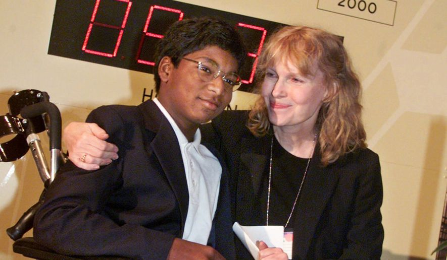 In this Sept. 27, 2000, file photo, actress Mia Farrow poses with her adopted son Thaddeus as they participate in the global summit on polio eradication at United Nations headquarters. Thaddeus Wilk Farrow, died, Wednesday, Sept 21, 2016, after being found seriously injured in his vehicle in Connecticut. The actress adopted Thaddeus, who contracted polio in an orphanage in Kolkata, India, and was paralyzed from the waist down. He was 27. (AP Photo/Richard Drew, File)