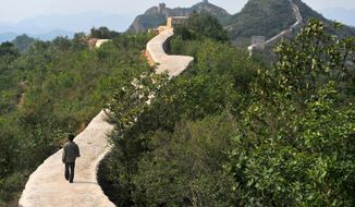 In this Wednesday, Sept. 21, 2016, file photo, a villager walks across a restored section of the Great Wall in Suizhong County in northeastern China's Liaoning Province. (Chinatopix via AP) ** FILE **