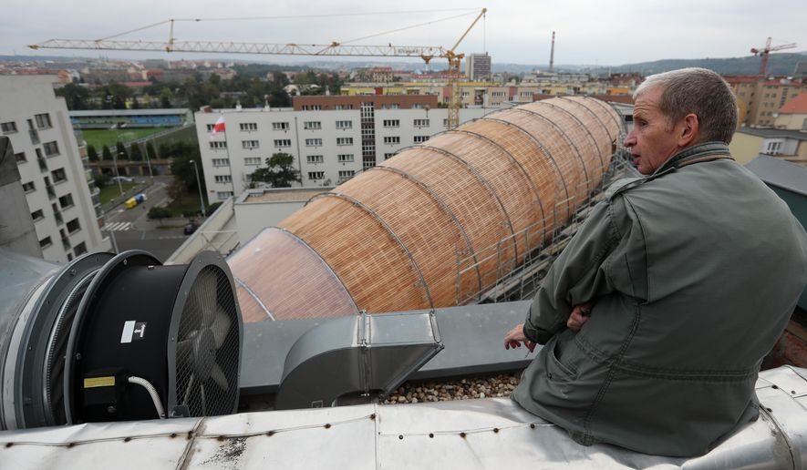 In this Monday, Sept. 19, 2016 photo Leos Valka, a co-creator, sits on a rooftop overlooking a giant object resembling a zeppelin airship at an arts center in Prague, Czech Republic. The 42-meter long and 10-meter wide ship is planned to seat some 120 people on its cascade steps. It will be used for authors' reading and debates about literature to complement exhibitions at the DOX Centre for Contemporary Art, one of the most innovative and challenging galleries in the Czech capital. (AP Photo/Petr David Josek)