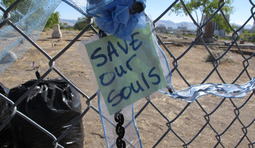 This Sept. 19, 2016 photo shows ribbons and notes tied to the fence around Hillside Cemeteryon the edge of downtown Reno, Nev.     Historic preservationists are outraged that the owner of the cemetary has obtained a permit and posted a notice of plans to exhume hundreds of graves and transfer the remains to another section of the cemetery so the land can be sold for potential development.  (AP Photo/Scott Sonner)