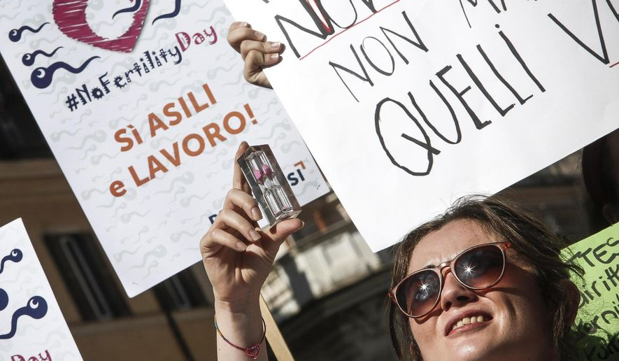 "A woman holds up an hourglass during a protest in front of the Italian Health Ministry during the launch of a 'Fertility Day' campaign, in Rome, Italy, Thursday, Sept. 22, 2016. Italy's efforts to combat infertility and reverse one of Europe's lowest birthrates have stumbled with an ad campaign denounced as sexist, racist and ignorant of the economic reasons why Italians aren't having babies. Earlier ads were criticized as sexist for featuring a woman holding an hourglass with the words ""Beauty doesn't have an age. Fertility does."" Writing on poster in the background reads ""Yes kindergartens and jobs!"" (Giuseppe Lami/ANSA via AP)"