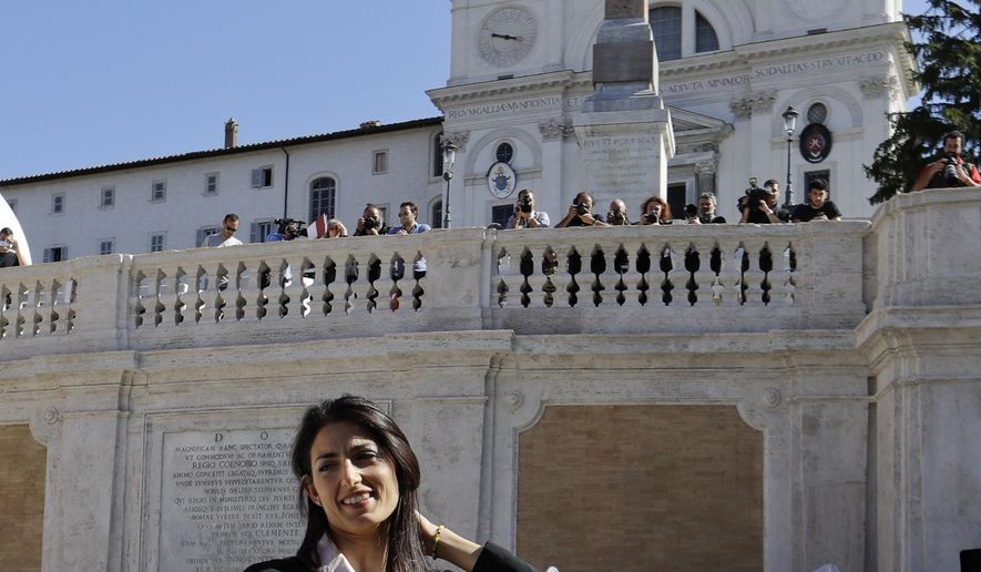 Rome's mayor Virginia Raggi poses for photographers in front of the world-famous Spanish Steps before the start of a press conference to present the reopening of the site at the end of 10 months of restoration works, in Rome, Thursday, Sept. 22, 2016. (AP Photo/Andrew Medichini)