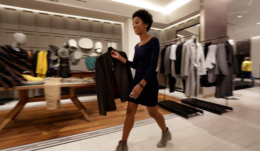 In this Wednesday, Sept. 7, 2016, photo, runner Aubrey Howard exchanges a garment for Associated Press writer Anne D'Innocenzio, at the Saks Fifth Avenue flagship store, in New York. With designer goods available online anytime, luxury retailers are adding more amenities and personal touches for in-person shopping. (AP Photo/Richard Drew)