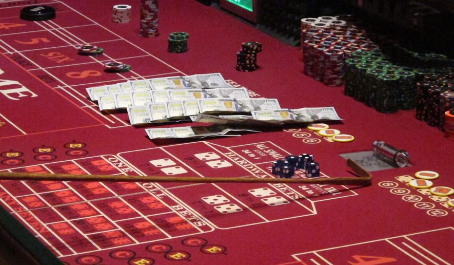 This June 24, 2016, photo shows cash, chips and dice on a craps table during a game at the Golden Nugget casino in Atlantic City, N.J. On Thursday, Sept. 22, 2016, the men who are proposing to build two new casinos in northern New Jersey near New York City, concluded the statewide ballot question that would authorize the projects will not pass, and ended their financial support for a campaign in its favor. (AP Photo/Wayne Parry)
