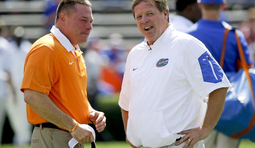 FILE - In this Sept. 26, 2015, file photo, Tennessee head coach Butch Jones, left, and Florida head coach Jim McElwain chat at midfield before an NCAA college football game in Gainesville, Fla. Jones is in his fourth season on the job and believes his Volunteers have never faced a defense quite as good as the one Florida brings to Neyland Stadium this weekend. (AP Photo/John Raoux, File)