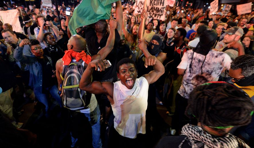 Protesters gather in Charlotte, N.C. on Thursday, Sept. 22, 2016.  The curfew has ended for Friday in Charlotte following a night of mostly peaceful protests of the shooting of Keith Lamont Scott by an officer. Charlotte Mayor Jennifer Roberts issued the curfew order Thursday night, to be in effect from midnight until 6 a.m. each day that the state of emergency continues. (Jeff Siner/The Charlotte Observer via AP)