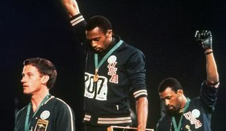 "U.S. athletes Tommie Smith, center, and John Carlos stare downward while extending gloved hands skyward during the playing of the Star Spangled Banner after Smith received the gold and Carlos the bronze for the 200 meter run at the Summer Olympic Games in Mexico City, Oct. 16, 1968. Australian silver medalist Peter Norman is at left. They called it a ""human rights salute.'' (AP Photo/File) **FILE**"
