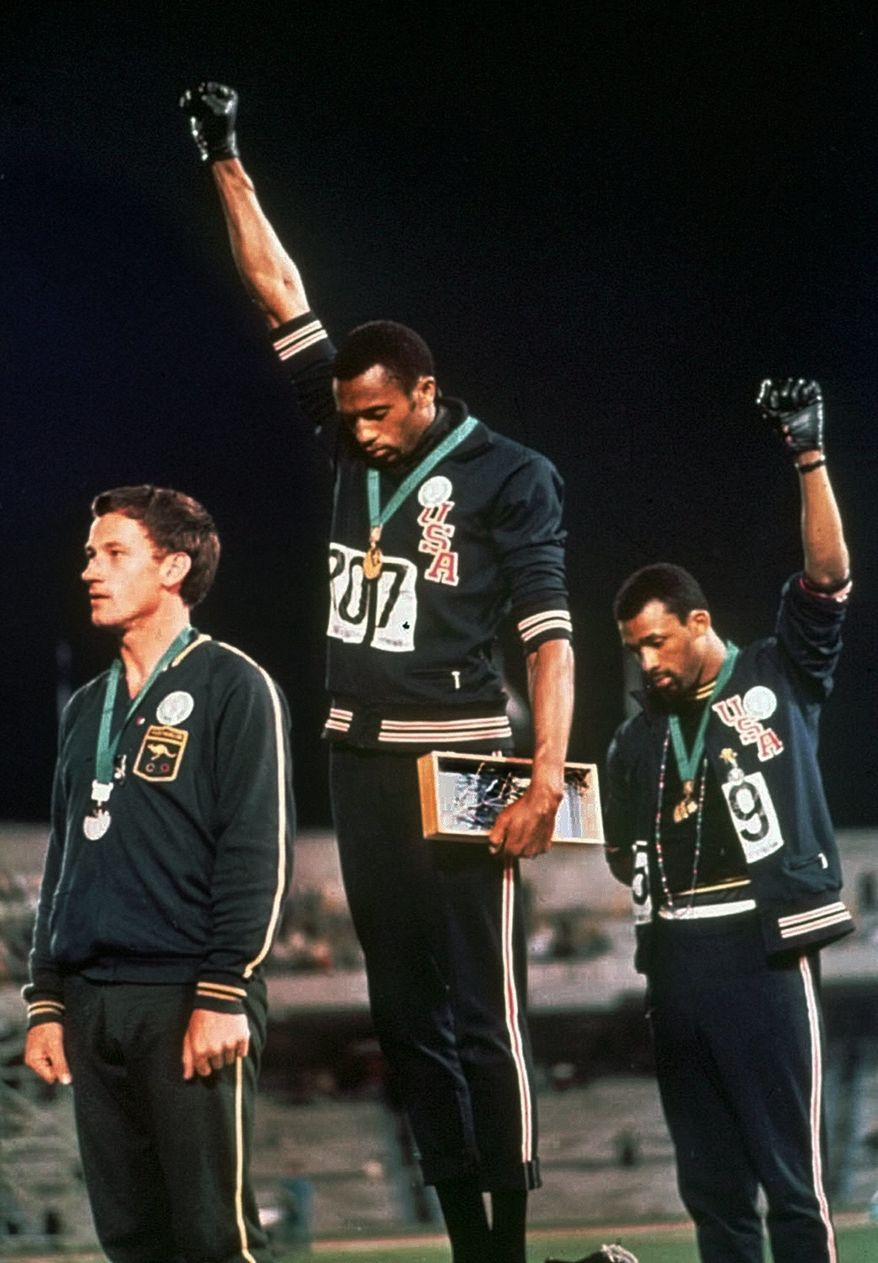 """U.S. athletes Tommie Smith, center, and John Carlos stare downward while extending gloved hands skyward during the playing of the Star Spangled Banner after Smith received the gold and Carlos the bronze for the 200 meter run at the Summer Olympic Games in Mexico City, Oct. 16, 1968. Australian silver medalist Peter Norman is at left. They called it a """"human rights salute.'' (AP Photo/File) **FILE**"""